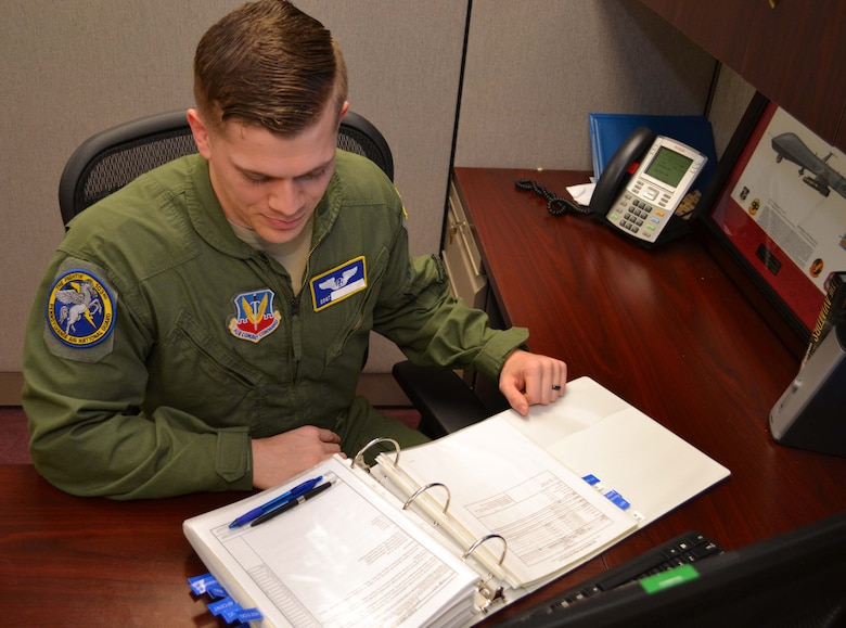 A sensor operator with the 111th Operations Group looks over a manual Jan. 27, 2016, in the 111th OG sensor operating section on Horsham Air Guard Station, Pennsylvania. Sensor operators play a critical role in the remotely-piloted aircraft mission at Horsham AGS, where the 111th Attack Wing operates the MQ-9 Reaper. (U.S. Air National Guard photo by Tech. Sgt. Andria Allmond)