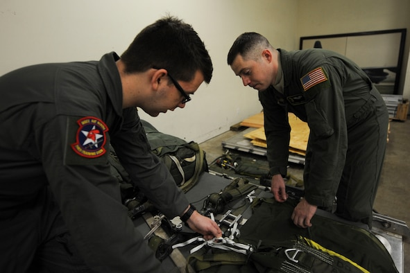(From right) U.S. Air Force Staff Sgt. Michael Anderson, 48th Airlift Squadron non-commissioned officer in charge of information operations and C-130 formal training unit loadmaster instructor, teaches U.S. Air Force Airman 1st Class Garrett Cornett, a 714th Training Squadron loadmaster student, how to properly secure cargo Jan. 27, 2016, at Little Rock Air Force Base, Ark. While completing all the required training needed to instruct in the C-130J formal training unit, Anderson identified errors in asset accountability preparation for the upcoming unit evaluation inspection. (U.S. Air Force photo by Airman 1st Class Mercedes Taylor)
