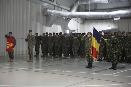 Marines with 3rd Battalion, 8th Marines salute alongside members of the Romanian Armed Forces during the transfer-of-authority ceremony aboard Mihail Kognalniceanu Air Base, Romania, Jan. 22, 2016. The rotational force of Marines and sailors gives U.S. European Command the continuous capability to integrate with NATO and partner nations in Eastern Europe. (U.S. Marine Corps photo by Cpl. Immanuel M. Johnson/Released)