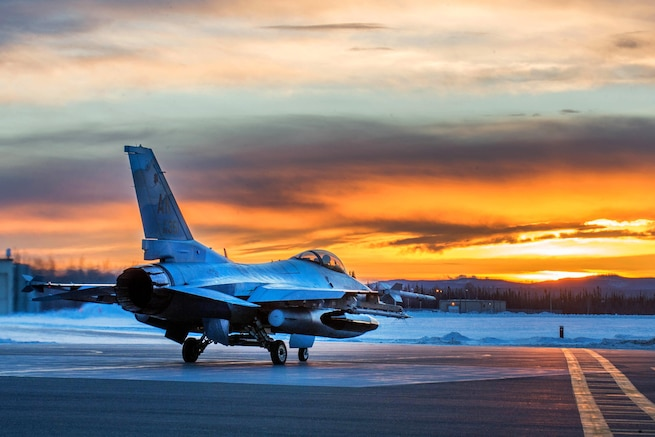 An Air Force F-16 Fighting Falcon aircraft prepares to take off shortly after sunrise from Eielson Air Force Base, Alaska, Jan. 24, 2016, to fly to Kadena Air Base, Japan, to participate in training exercises. The Falcon is assigned to the 18th Aggressor Squadron. Air Force photo by Staff Sgt. Shawn Nickel