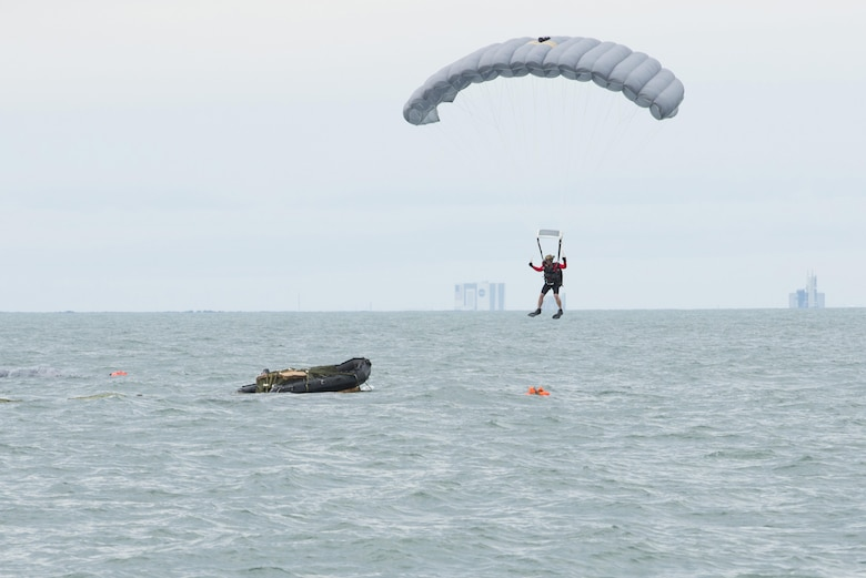 An Air Force Reserve pararescueman descends into the Atlantic Ocean from a C‐17 Globemaster III in an effort to recover a NASA astronaut as part of an exercise Jan. 14, 2016, off the shore of Cape Canaveral Air Force Station, Fla. The 45th Operations Group's Detachment 3 joined NASA's Commercial Crew Program; Air Force pararescuemen; combat rescue officers; and survival, evasion, resistance and escape specialists to practice recovering astronauts quickly and safely in the event they would need to abandon their spacecraft. (U.S Air Force photo/Matthew Jurgens)