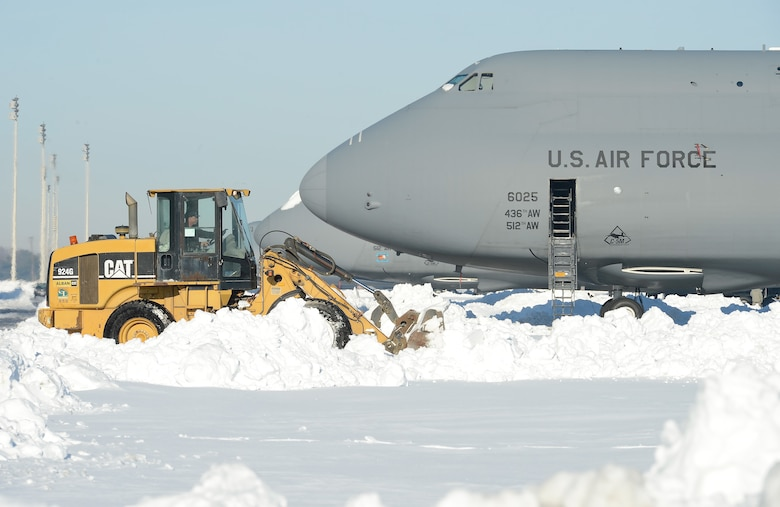 A Caterpillar front loader clears the Dover Air Force Base, Del., flightline near a C‐5M Super Galaxy airlift aircraft, assigned to the 436th Airlift Wing, during recovery operations Jan. 25, 2016, after Winter Storm Jonas. Heavy equipment cleared the open areas while hand shovels were used to clear the 22 inches of accumulated snow from around the aircraft. (U.S. Air Force photo/Greg L. Davis)