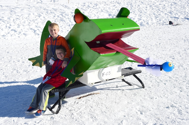 Landen and Casey Rup pose with their homemade cardboard sled before the Snofest cardboard derby Jan. 23, 2016, at Keystone Resort, Colo. Snofest is a military appreciation event at Keystone Resort for the Front Range Military Bases, that included a cardboard derby with nine categories including biggest crowd pleaser, fastest and most creative. (U.S. Air Force photo by Airman 1st Class Gabrielle Spradling/Released)