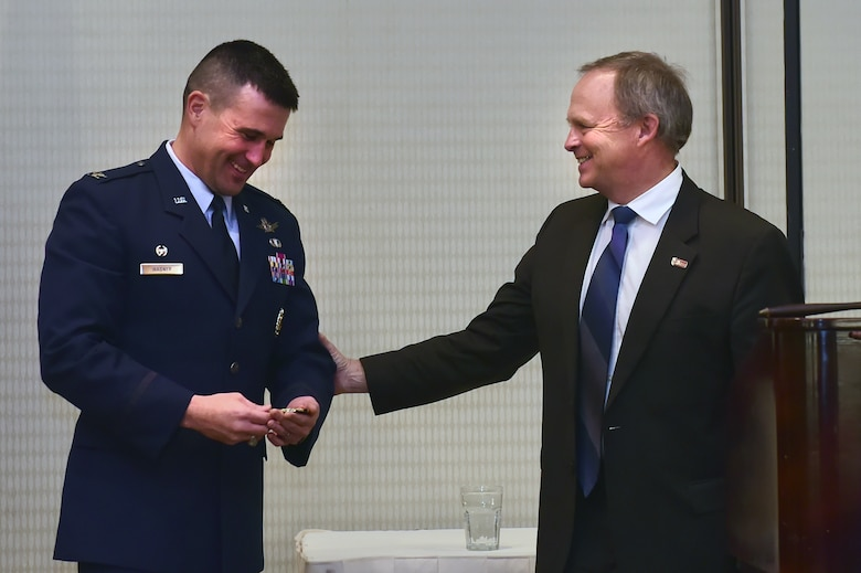 Col. John Wagner, 460th Space Wing commander, receives a coin from Kevin Hougen, Aurora Chamber of Commerce president, during the State of the Base luncheon Jan. 29, 2015, at the DoubleTree by Hilton in Aurora, Colo. The luncheon gives Buckley Air Force Base leaders the opportunity to connect with community leaders, giving them information on upcoming projects and the base's economic impact. (U.S. Air Force photo by Airman 1st Class Luke W. Nowakowski/Released)