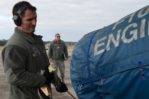 U.S. Air Force Tech. Sgt. Bennett Koenig, assigned to the 169th Logistics Readiness Squadron, loads cargo into a Georgia Air National Guard C-130H3 Hercules on the flight line at McEntire Joint National Guard Base, S.C., Jan. 21, 2016 as Chief Master Sgt. Lanny Cobb (background), a Wing Inspection Team member assigned to the 169th Fighter Wing, evaluates the equipment loading and deployment processes. The evaluation is part of a mid-point inspection that is a mandatory measure of the Air Force Inspection System. (U.S. Air National Guard photo by Senior Airman Ashleigh Pavelek)