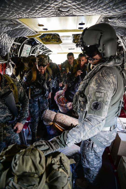 U.S. Army Sgt. Jesse Gomez, 1-228th Aviation Regiment crew chief helps Honduran troops load a U.S. Army CH-47 Chinook helicopter in the Gracias a Dios Department (state), Honduras, Jan. 13, 2016. The troops were transported in support of Operation CARAVANA, a mission to reach austere locations department and degrade the trafficking of illicit materials there. (U.S. Air Force photo by Senior Airman Westin Warburton/Released)