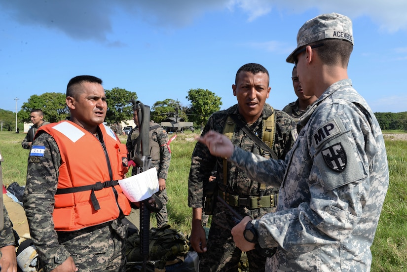 U.S. Army Sgt. Saul Acevedo, Joint Task Force-Bravo Joint Security Forces, discusses boarding procedures with Honduran soldiers, in the Gracias a Dios Department (state), Honduras, Jan. 13, 2016. Acevedo acted as Spanish-speaking a liaison between the U.S. Service members and Honduran troops during the U.S. support to Operation CARAVANA, a Honduran effort to disrupt drug trafficking in hard to reach locations in eastern Honduras. (U.S. Air Force photo by Senior Airman Westin Warburton/Released)
