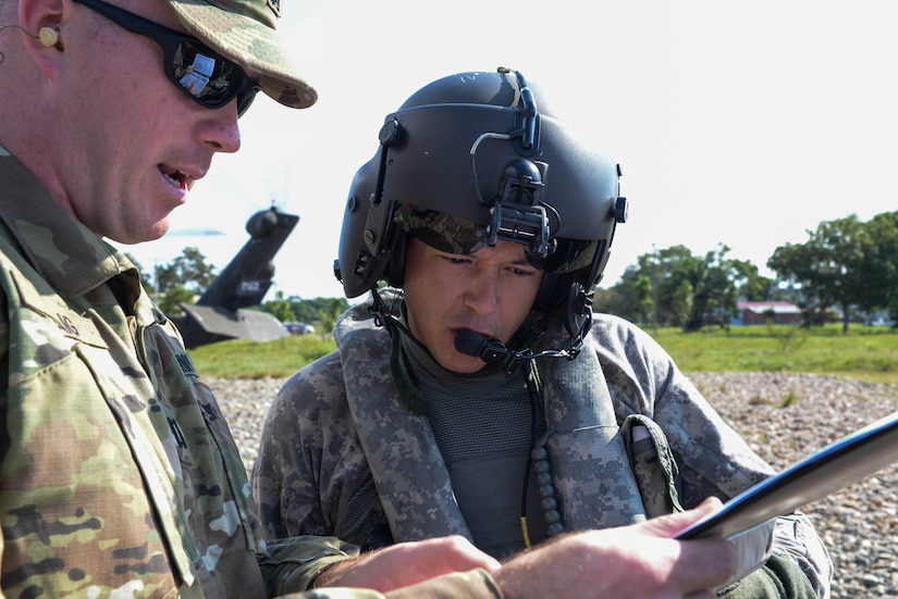 U.S. Army Capt. Cameron Craig, Joint Task Force-Bravo tactical team officer in charge, shows a flight itinerary to Sgt. Ruben Ramos, 1-228th Aviation Regiment UH-60 Blackhawk helicopter crew chief in the Gracias a Dios Department (state), Honduras, Jan. 13, 2016. The Army supported the Honduran troop movement, Operation CARAVANA, by transporting Honduran troops to various points the department. (U.S. Air Force photo by Senior Airman Westin Warburton/Released)
