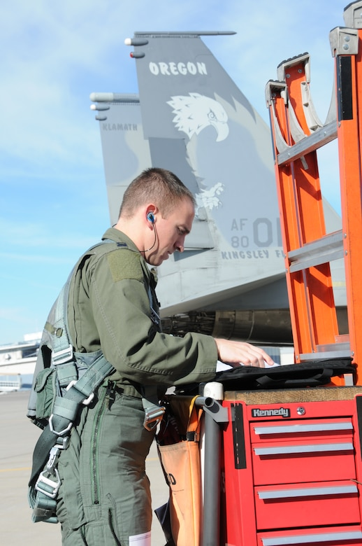 U.S. Air Force Capt. Alexander Frank, F-15 student pilot, reviews the forms prior to a check ride in the F-15 Eagle Jan. 27, 2016 at Kingsley Field in Klamath Falls, Ore.  During this flight, Frank had to demonstrate his ability to fly in inclement weather using the aircraft instruments.  (U.S. Air National Guard photo by Tech. Sgt. Jefferson Thompson/released)