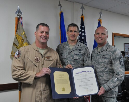 Brig. Gen. Daniel Orcutt, 380th Air Expeditionary Wing commander, Col. Johnny Barnes, 380 AEW vice commander, and Chief Master Sgt. Charles Mills, 380 AEW command chief, left to right respectively, pose for a group photo after the 380th is awarded the Meritorious Unit Award during a ceremony at an undisclosed location in Southwest Asia, Jan. 18, 2016. The award recognizes Air Force active duty, Reserve and Guard units for exceptionally meritorious conduct in the performance of outstanding achievement or service in direct support of combat operations for at least 90 continuous days during the period of military operations against an armed enemy of the U.S. on or after Sept. 11, 2001. (U.S. Air Force photo by Staff Sgt. Kentavist P. Brackin/Released)