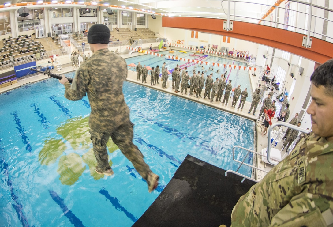 U.S. Army Master Sgt. Joe Medrano, a senior military instructor for Clemson University's Reserve Officers' Training Corps program from Presidio, Texas, watches as a cadet launches - blindfolded and carrying an M16 - from a five-meter diving board during the Combat Water Survival Test, Jan. 28, 2016. (U.S. Army photo by Staff Sgt. Ken Scar)