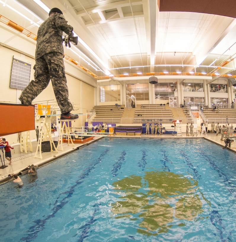 A blindfolded U.S. Army Reserve Officers' Training Corps cadet steps off a five-meter diving board while taking the Combat Water Survival Test at Clemson University, Jan. 28, 2016. (U.S. Army photo by Staff Sgt. Ken Scar)