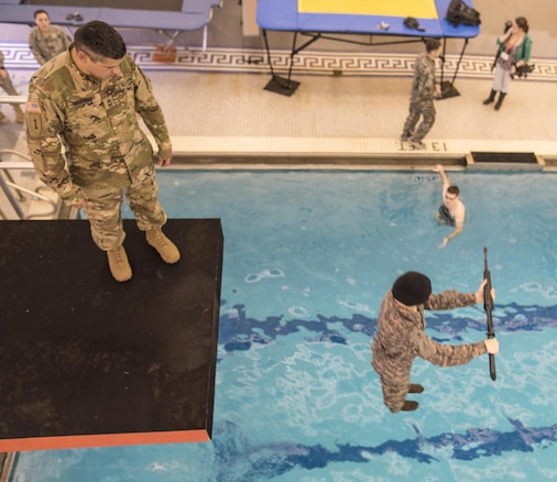 U.S. Army Master Sgt. Joe Medrano, a senior military instructor for Clemson University's Reserve Officers' Training Corps program from Presidio, Texas, watches as a cadet drops - blindfolded and carrying an M16 - from a 5-meter diving board into a pool during the Combat Water Survival Test, Jan. 28, 2016. (U.S. Army photo by Staff Sgt. Ken Scar)