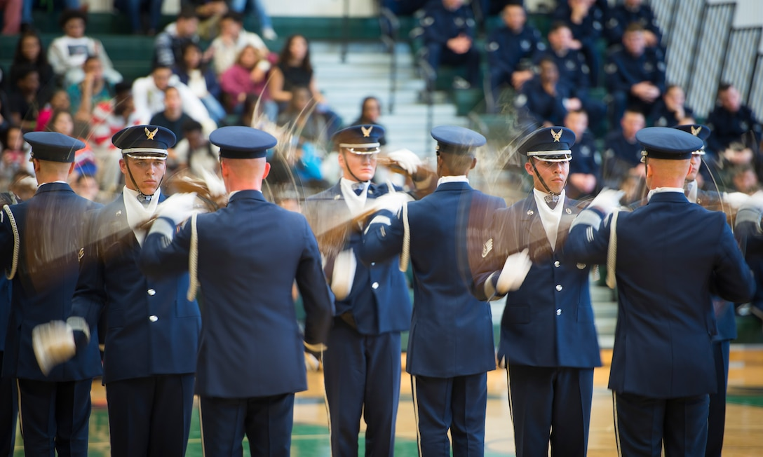 Members of the United States Air Force Honor Guard drill team spin their M1 Garand rifles at Oak Ridge High School, Orlando, Fla. Jan. 21, 2016. The Drill Team performed in front of hundreds of students and afterward held a training session with the Junior Reserve Officer Training Corps cadets. (U.S. Air Force photo by Staff Sgt. Chad C. Strohmeyer/Released)