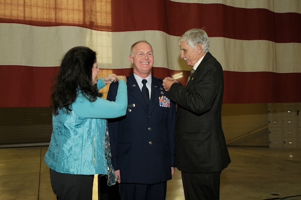 U.S. Air Force Lt. Col. Allan R. Cecil (center), deputy commander of the 145th Maintenance Group, has the rank of colonel pinned onto his uniform by his spouse and retired Brig. Gen. Fisk Outwater during a ceremony held in his honor at the North Carolina Air National Guard Base, Charlotte Douglas International Airport, Jan. 9, 2016. In 1977, at the rank of Master Sergeant, Cecil was commissioned as a weather officer. (U.S. Air National Guard photo by Staff Sgt. Julianne M. Showalter/Released)