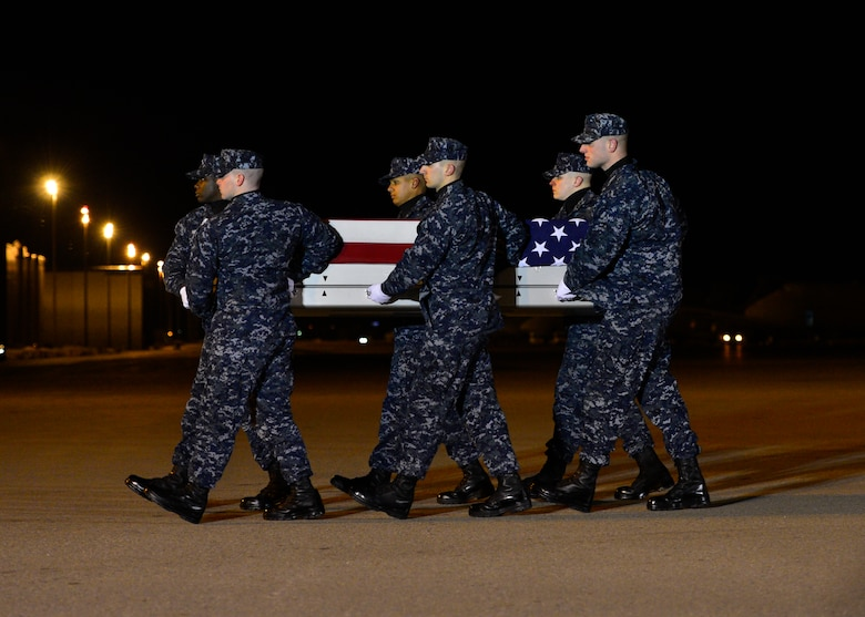 A U.S. Navy carry team transfers the remains of U.S. Navy civilian Blane D. Bussell, a native of Virginia, during a dignified transfer Jan. 29, 2016, at Dover Air Force Base, Del. Mr. Bussell was assigned to Naval Support Activity, Bahrain. (U.S. Air Force photo/Senior Airman Zachary Cacicia)