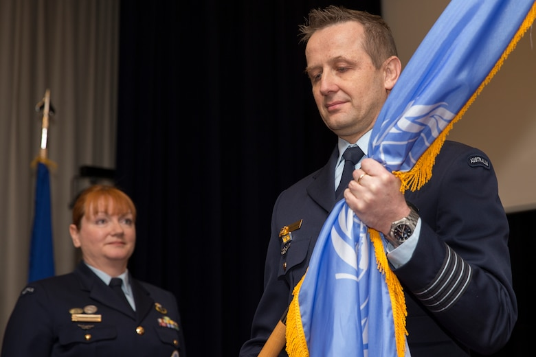 Royal Australian Air Force Group Captain Michael Jansen, incoming United Nations Command (Rear) commander, receives the guidon during a change of command ceremony at Yokota Air Base, Japan, Jan. 26, 2016. The UNC (Rear) has historically been commanded by a U.S. Army Colonel however since 2010 the command has been filled by an Australian Air Force officer with this change of command assigning the fourth successive Australian commander. (U.S. Air Force photo by Osakabe Yasuo/Released)
