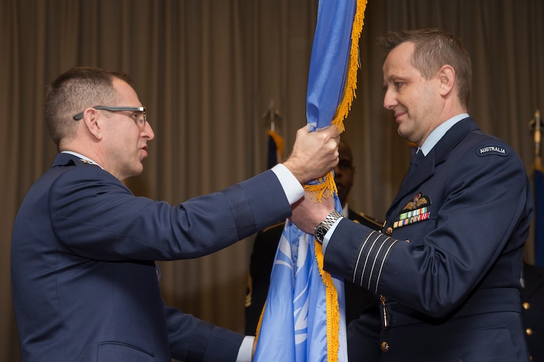 (Right to left) Royal Australian Air Force Group Captain Michael Jansen, incoming United Nations Command (Rear) commander, receives the guidon from U.S. Air Force Maj. Gen. James Slife, deputy chief of staff for United Nations Command and U.S. Forces Korea at Yongsan Garrison, Seoul, South Korea, during a change of command ceremony at Yokota Air Base, Japan, Jan. 26, 2016. The UNC (Rear) has historically been commanded by a U.S. Army Colonel however since 2010 the command has been filled by an Australian Air Force officer with this change of command assigning the fourth successive Australian commander. (U.S. Air Force photo by Osakabe Yasuo/Released)