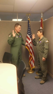 U.S. Air Force Col. Todd Mitton (left), Missouri National Guard A-3 director of operations, reads the oath of enlistment to his brother-in-law, Chief Master Sgt. David Schultz, 139th Operations Group superintendent, on Jan. 28, 2016 at Rosecrans Air National Guard Base. (Courtesy photo)