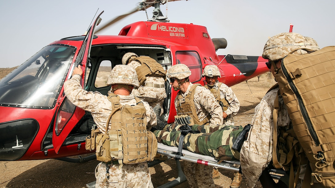 U.S Marines with Special Purpose Marine Air-Ground Task Force Crisis Response-Africa load a simulated casualty to a helicopter during a medivac rehearsal with the Compagnie Fusilier de Marin Commando in Thies, Senegal, June 21, 2016. This is the first time Marines and the COFUMACO have used a helicopter for medical assistance during training in Senegal. This new capability saves valuable time should an injury occur during live-fire ranges.
