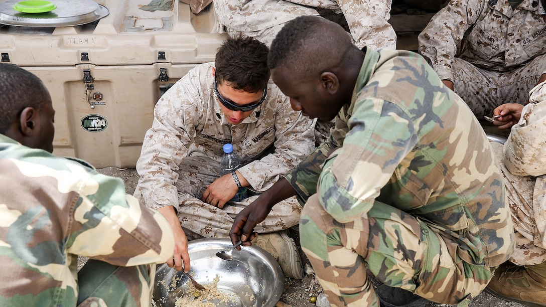 Sgt Ryan Underwood, a rifleman with Special Purpose Marine Air-Ground Task Force Crisis Response-Africa, shares lunch with the Compagnie Fusilier de Marin Commando in Thies, Senegal, June 22 2016. Marines and the COFUMACO conducted a three-week training exercise that included advanced combat firing techniques, a machine gun range and a live-fire platoon attack range.