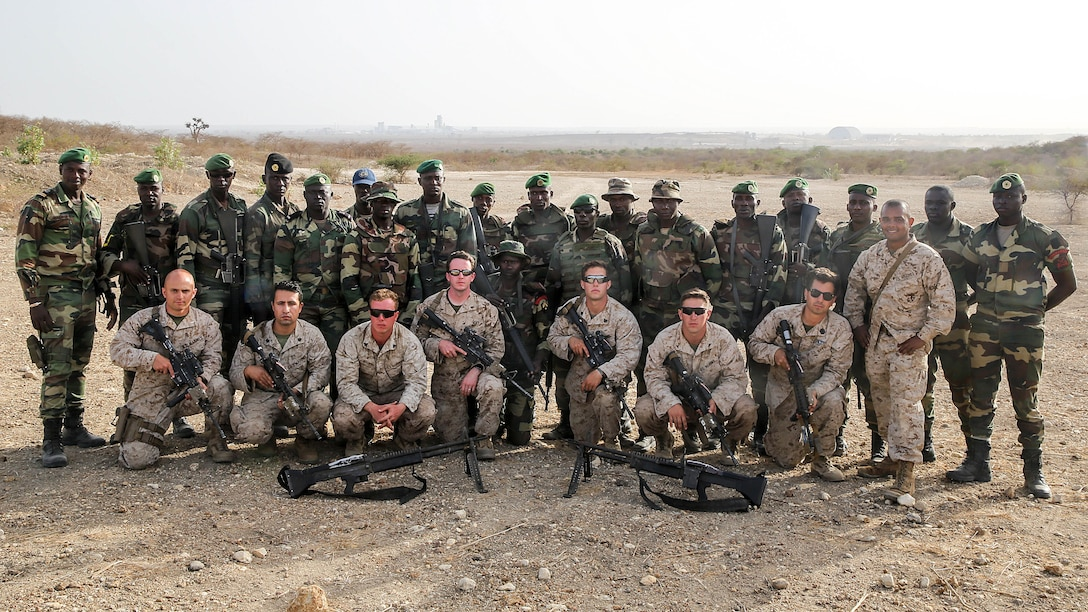 Marines with Special Purpose Marine Air-Ground Task Force Crisis Response-Africa  pose for a picture with the Compagnie Fusilier de Marin Commando in Thies, Senegal, June 22, 2016. Marines and the COFUMACO conducted a three-week training exercise that included advanced combat firing techniques, a machine gun range and a live-fire platoon attack range.