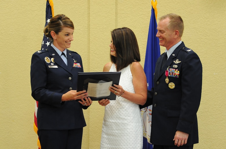 Col. Michele Edmondson, 81st Training Wing commander, presents an Air Force certificate of appreciation to Mary Scarborough, the spouse of Col. Dennis Scarborough, 81st TRW vice commander, during his retirement ceremony at the Bay Breeze Event Center June 28, 2016, on Keesler Air Force Base, Miss. Scarborough retired with 27 years of military service. He has served multiple tours as an F-15C instructor and evaluator and has held positions in the fields of defense policy, operational plans, safety and aircraft maintenance. He has commanded at the squadron level and served as an operations group deputy commander. (U.S. Air Force photo by Kemberly Groue/Released)