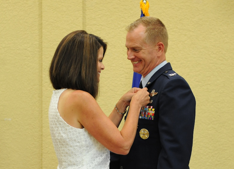 Mary Scarborough presents a retirement pin to her husband, Col. Dennis Scarborough, 81st Training Wing vice commander, during his retirement ceremony at the Bay Breeze Event Center June 28, 2016, on Keesler Air Force Base, Miss. Scarborough retired with 27 years of military service. He has served multiple tours as an F-15C instructor and evaluator and has held positions in the fields of defense policy, operational plans, safety and aircraft maintenance. He has commanded at the squadron level and served as an operations group deputy commander. (U.S. Air Force photo by Kemberly Groue/Released)