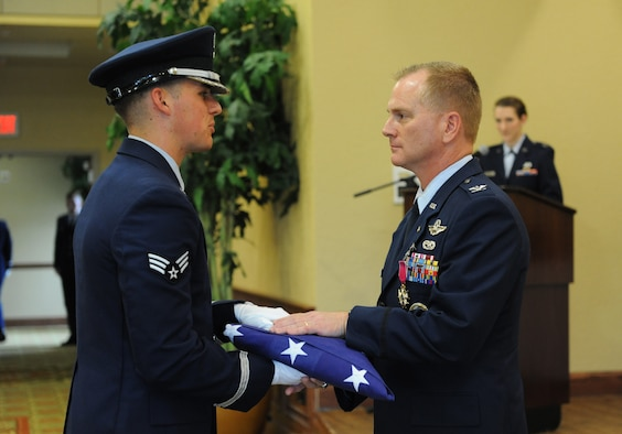 Senior Airman Dylan Anderson, Keesler Honor Guard member, presents the U.S. flag to Col. Dennis Scarborough, 81st Training Wing vice commander, during his retirement ceremony at the Bay Breeze Event Center June 28, 2016, on Keesler Air Force Base, Miss. Scarborough retired with 27 years of military service. He has served multiple tours as an F-15C instructor and evaluator and has held positions in the fields of defense policy, operational plans, safety and aircraft maintenance. He has commanded at the squadron level and served as an operations group deputy commander. (U.S. Air Force photo by Kemberly Groue/Released)