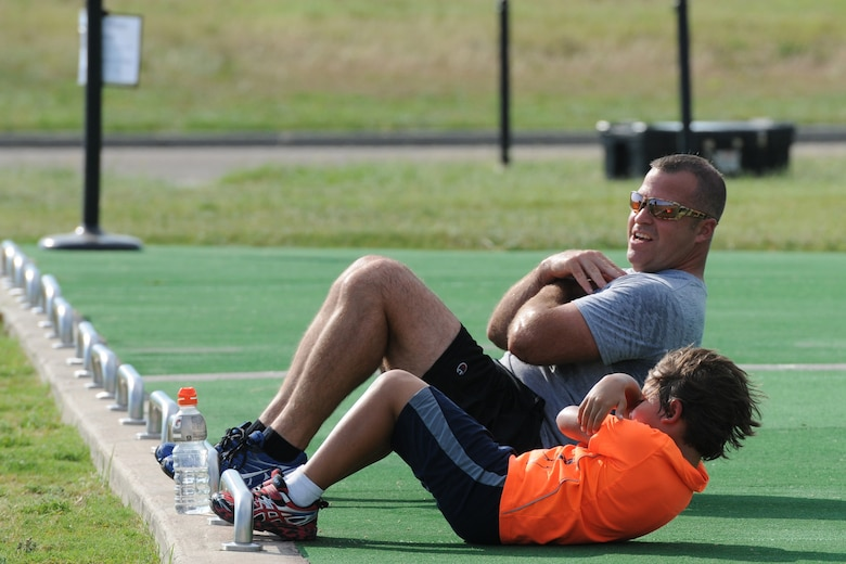 Chief Master Sgt. Derek Fromenthal, 338th Training Squadron superintendent, and his son, D'Anthony, do sit-ups during the Obstacle Warrior Dash 5K at the Triangle track June 27, 2016, on Keesler Air Force Base, Miss. The 81st Force Support Squadron-sponsored event involved participants completing a 5K run then making their way through eight different obstacles. (U.S. Air Force photo by Kemberly Groue/Released)