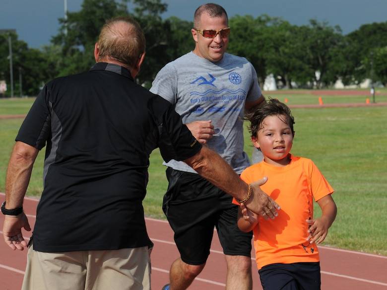 Chief Master Sgt. Derek Fromenthal, 338th Training Squadron superintendent, and his son, D'Anthony, complete a one-mile run and obstacle course during the Obstacle Warrior Dash 5K at the Triangle track June 27, 2016, on Keesler Air Force Base, Miss. The 81st Force Support Squadron-sponsored event involved participants completing a 5K run then making their way through eight different obstacles. (U.S. Air Force photo by Kemberly Groue/Released)