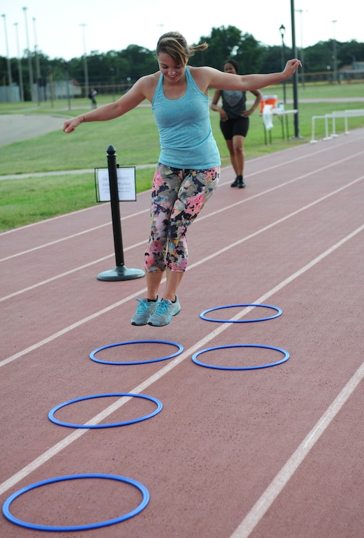 Staff Sgt. Haley May, 335th Training Squadron student, jumps through a 12-foot agility ring course during the Obstacle Warrior Dash 5K at the Triangle track June 27, 2016, on Keesler Air Force Base, Miss. The 81st Force Support Squadron-sponsored event involved participants completing a 5K run then making their way through eight different obstacles. (U.S. Air Force photo by Kemberly Groue/Released)