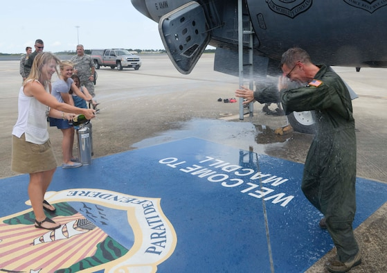 Col. Daniel Tulley, right, commander of the 6th Air Mobility Wing, is sprayed with water and champagne by his family during his fini flight at MacDill Air Force Base, Fla., June 28, 2016. Tulley's two-year tenure comes to an end as he prepares to relinquish command on July 8.