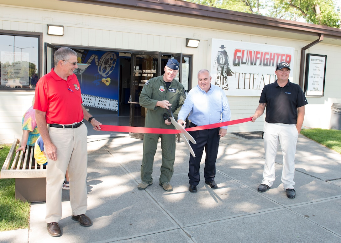 Col. Brian McCarthy, 366th Operations Group commander, cuts a ribbon during the Gunfighter Theater re-opening July 1, 2016, at Mountain Home Air Force Base, Idaho. The theater renovations consisted of improvements to audio visual equipment, stage curtains, the roof, restrooms and more. (U.S. Air Force photo by Airman 1st Class Chester Mientkiewicz/Released)