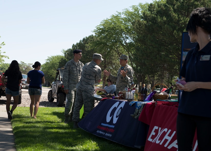 Maj. Thaddeus Speed, 366th Medical Squadron Bio Flight Commander, talks to individuals interested in the Mountain Home Air Force Base Running Club during the 366th Force Support Squadron summer social and Gunfighter Theater re-opening July 1, 2016, at Mountain Home Air Force Base, Idaho. The summer social consisted of bouncy houses, prizes, food and the introduction of the new social club programs. (U.S. Air Force photo by Airman 1st Class Chester Mientkiewicz/Released)