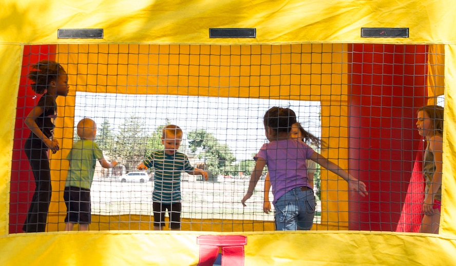 Kids jump in a bouncy house during the 366th Force Support Squadron summer social and Gunfighter Theater re-opening July 1, 2016, at Mountain Home Air Force Base, Idaho. The re-opening of the theater has many excited as movies will be shown again throughout the day. For more information and a movie schedule go to: http://www.mhafbfun.com/theater/schedule.html (U.S. Air Force photo by Airman 1st Class Chester Mientkiewicz/Released)