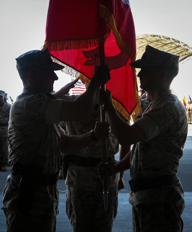 Lt. Col. William Maples (right) passes the flag to Lt. Col. Chad Vaughn (left) as he relinquishes command of the transitioning squadron during a re-designation and change of command ceremony aboard Marine Corps Air Station Yuma, Ariz., June 30. During the ceremony, Marine Attack Squadron (VMA) 211 transitioned to Marine Fighter Attack Squadron (VMFA) 211 making it the first AV-8B Harrier squadron to become an F-35B Lightning II Joint Strike Fighter squadron. (U.S. Marine Corps photo by Lance Cpl. Harley Robinson/Released.)