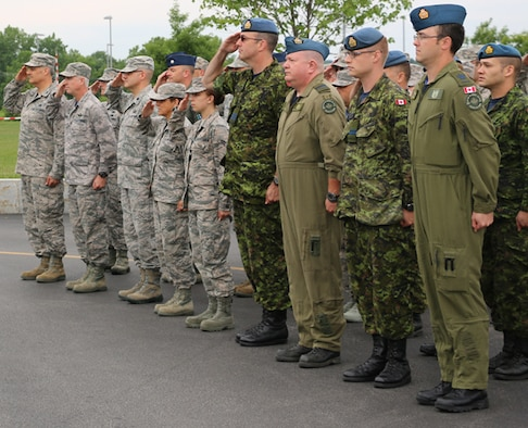 New York Air National Guardsmen and Canadian Forces members at the Eastern Air Defense Sector salute on Friday, July 1, as the Canadian flag is raised. The flag-raising ceremony was in honor of Canada Day, which is celebrated on July 1. EADS is a NORAD headquarters unit, where New York Air National Guardsmen and Canadian Forces work side by side every day.