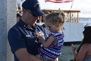 Chief Petty Officer Nathan Purinton, executive officer of the Coast Guard Cutter Haddock, embraces his daughter after returning to home port at Coast Guard Sector San Diego, Calif., July 3, 2016. Coast Guard photo by Petty Officer 3rd Class Joel Guzman