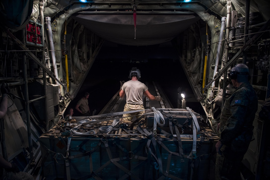 A U.S. Air Force loadmaster from the Alaska Air National Guard's 144th Airlift Squadron prepares to offload cargo from a C-130 Hercules after landing in Iraq June 17, 2016. The transport mission was one of the last combat missions during the 144th AS's final C-130 deployment. (U.S. Air Force photo by Staff Sgt. Douglas Ellis/Released)