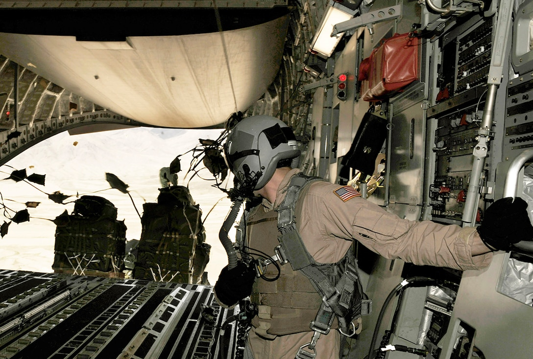 Senior Airman Rory Nowosielski stands on the ramp as container delivery system bundles exit the aircraft during a high-altitude airdrop mission in a C-17 Globemaster III Feb. 14 over Afghanistan. Airman Nowosielski is a C-17 loadmaster with the 816th Expeditionary Airlift Squadron.