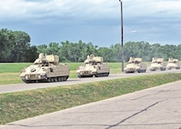 M2 Bradley Fighting Vehicles from 1st Battalion, 5th Field Artillery Regiment, 1st Armored Brigade Combat Team, 1st Infantry Division, convoy to the Fort Riley rail yard before being loaded onto rail cars June 24.