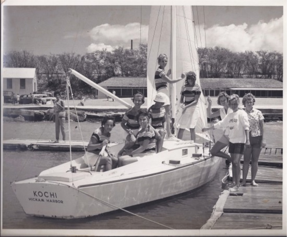 """The Wet Hens pose with """"The Kochi"""" following a refit of the vessel, circa 1962, at Hickam Harbor. In 1961, the group was founded by a group of Air Force wives that learned to sail from then harbormaster, Lou Foster. Early in their training, he referred to his students as a bunch of """"wet hens,"""" and the name stuck. After learning to sail, the women wanted to share their newfound skills with other women. So those first """"Wet Hens"""" started a tradition that has lasted 55 years. (Courtesy Photo)"""