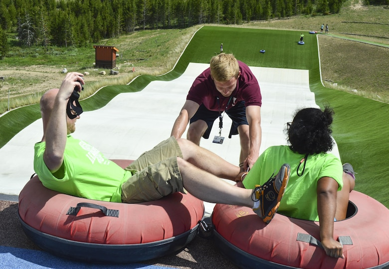 Two members of the Youth Leadership Camp, sponsored by Air Force Services Agency Child and Youth Programs and hosted by Buckley Air Force Base, prepare to slide down a tube activity during a challenge June 27 – July 1 at the Snow Mountain Ranch in Granby, Colo. Youth from around the world came together to learn leadership techniques and build confidence for their future years of high school and beyond. (U.S. Air Force photo by Tech. Sgt. Nicholas Rau)