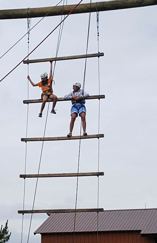 Two members of the Youth Leadership Camp, sponsored by Air Force Services Agency Child and Youth Programs and hosted by Buckley Air Force Base, climb an obstacle during a challenge June 27 – July 1 at the Snow Mountain Ranch in Granby, Colo. Youth from around the world came together to learn leadership techniques and build confidence for their future years of high school and beyond. (U.S. Air Force photo by Tech. Sgt. Nicholas Rau)