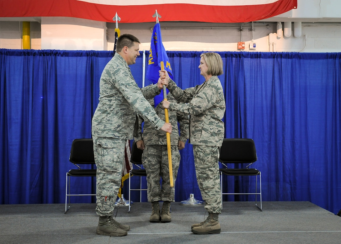 Lt. Col. Catherine A. Hutson, 174th Attack Wing (ATKW) Maintenance Group commander, receives the group's guidon from Col. Michael R. Smith, 174th ATKW commander, during an assumption of command ceremony held at Hancock Field Air National Guard Base, June 30. (U.S. Air National Guard photo by Tech. Sgt. Jeremy Call/Released)