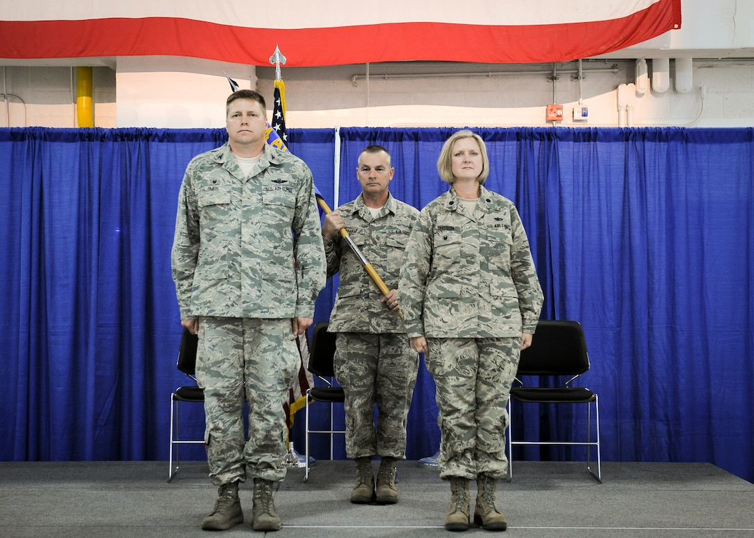 Col. Michael R. Smith, 174th Attack Wing commander, stands at attention with newly appointed Maintenance Group Commander, Lt. Col. Catherine A. Hutson during an assumption of command ceremony held at Hancock Field Air National Guard Base, Thursday, June 30. (U.S. Air National Guard photo by Tech. Sgt. Jeremy Call/Released)