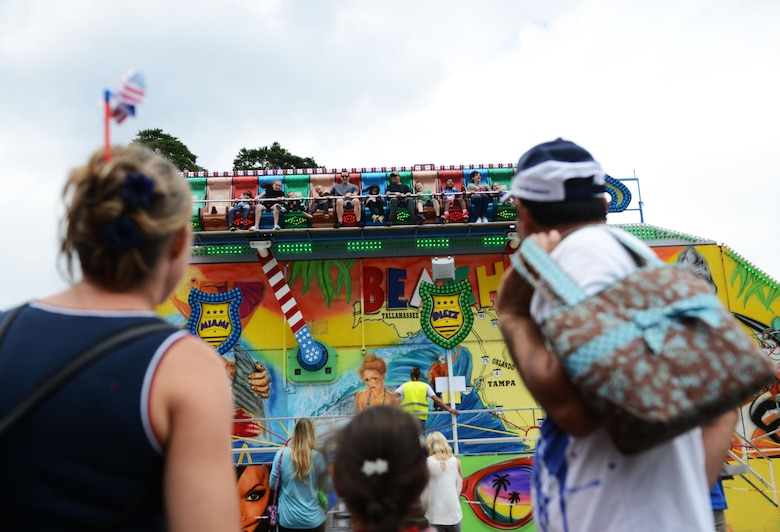 A family watches carnival goers enjoy a ride during the Freedom Fest 2016 at Ramstein Air Base, Germany, July 4, 2016. The Independence Day celebration included a variety of foods, games, rides and fireworks for Kaiserslautern Military Community members. (U.S. Air Force Photo/ Airman 1st Class Joshua Magbanua)