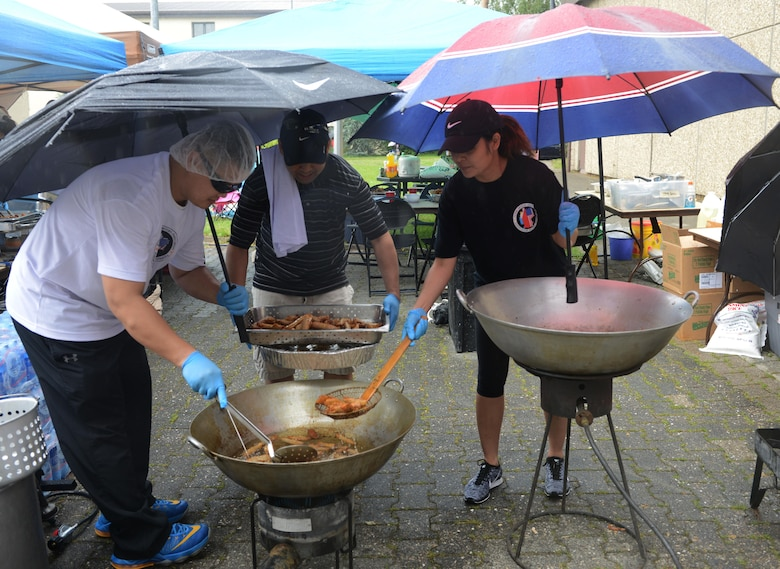 Volunteers with the Filipino-American Association of the Kaiserslautern Military Community fry egg rolls in the rain during Freedom Fest 2016 at Ramstein Air Base, Germany, July 4, 2016. The Independence Day celebration included a variety of foods, games, rides and fireworks for KMC members.  (U.S. Air Force Photo/ Airman 1st Class Joshua Magbanua)