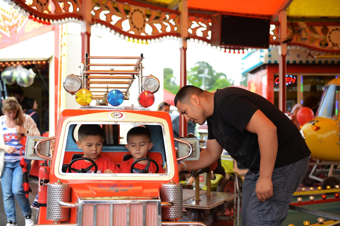 A man sets up his children in a carousel ride during the Freedom Fest 2016 at Ramstein Air Base, Germany, July 4, 2016. The Independence Day celebration included a variety of foods, games, rides and fireworks for Kaiserslautern Military Community members. (U.S. Air Force Photo/ Airman 1st Class Joshua Magbanua)